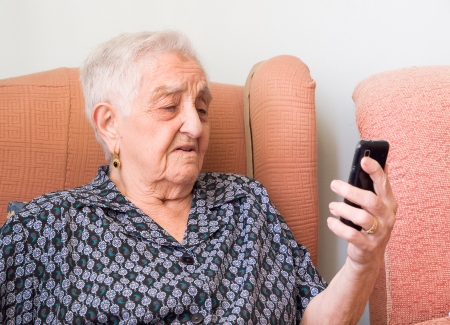Elderly woman looking at a smartphone with confused expression. The woman is in her home. photo