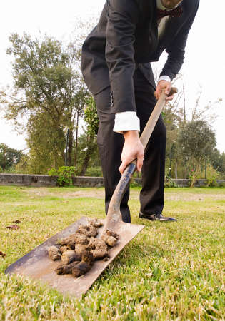 droppings: Businessman picking up droppings with a shovel outdoors Stock Photo