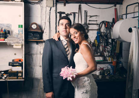 Married couple in a garage. the woman is smiling and man is facing up. photo