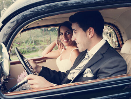 Bride and groom inside a classic car. They are happy. photo
