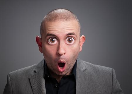 occhi sbarrati: Uomo d'affari con espressione di sorpresa La foto ha un ritocco digitale con gli occhi spalancati