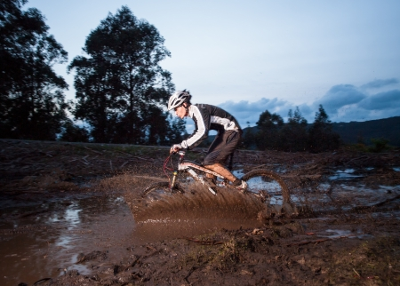 Rider in action at a mud puddle in nature outdoors Stock Photo