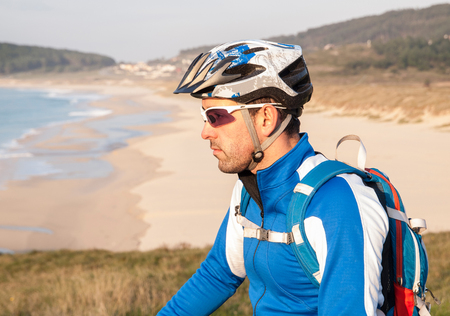 Cyclist in nature looking aside. The man is outside photo