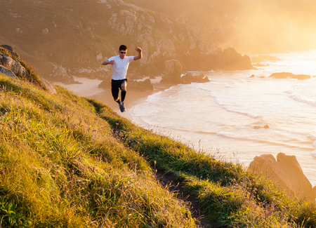 Man practicing trail running and leaping in a path in the coast in a sunny day photo