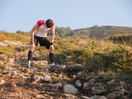 Trail runner exhausted. Man is taking air.