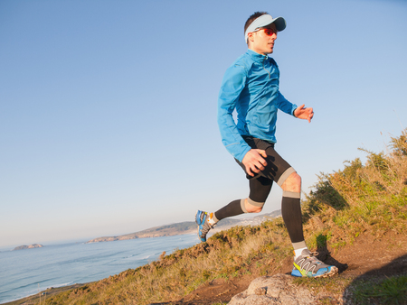 Man practicing trail running with a coastal landscape