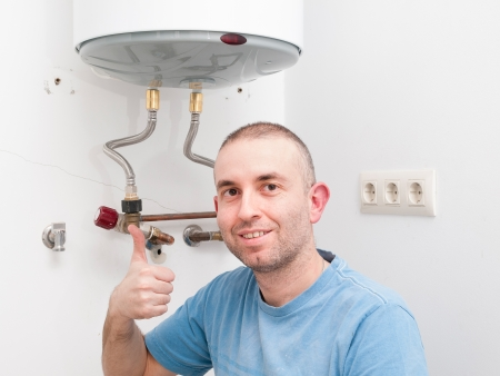 ok symbol: Plumber Man expressing positivity with ok symbol with hand. Man has repaired an electric boiler.