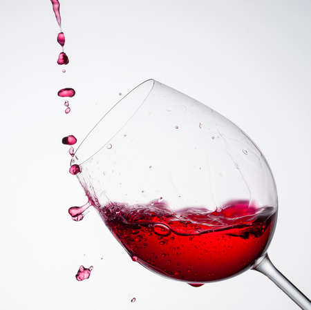 Wine pouring into a glass in square composition and white background photo