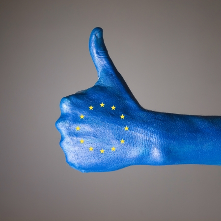 Hand painted with the flag of European Community,  expressing positivity and isolated on gray background photo