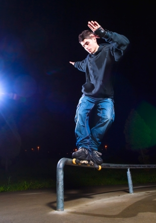 kerb: Young man practicing rollerskating. The young is grind a railing. Editorial