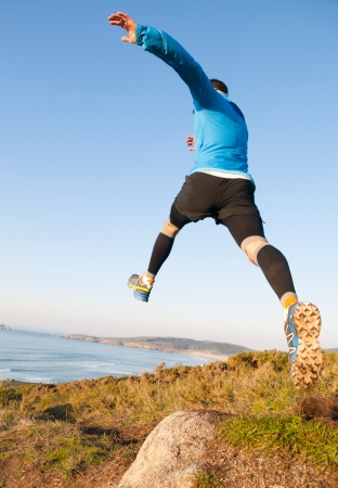 Man giving a big jump while practicing trail running with a coastal landscape in the background. Stock Photo