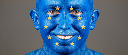 Man with his face painted with the flag of European Union. The man is smiling and photographic composition leaves only half of the face. photo
