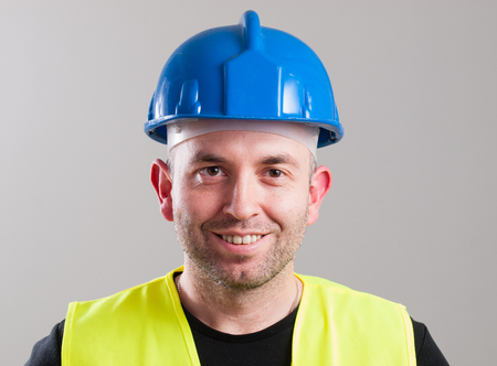 Portrait of a worker expressing positivity isolated on grey background photo