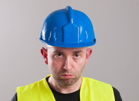 expressing negativity: Portrait of a worker expressing negativity and isolated on dark background