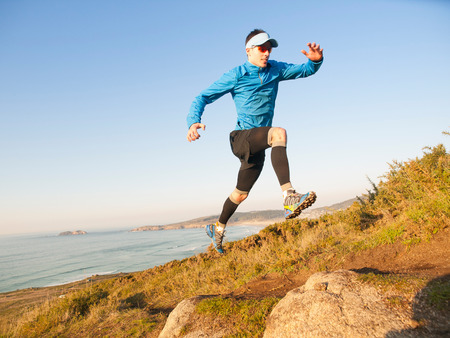 Man practicing trail running with a coastal landscape in the background photo