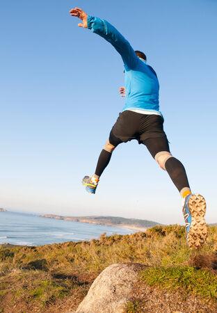 Hombre que da un gran salto al practicar trail running con un paisaje de la costa en el fondo.