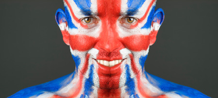 Man with his face painted with the flag of United Kingdom.  photo