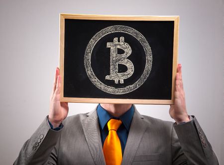 Businessman hiding his face behind bitcoin symbol and isolated on dark background Stock Photo
