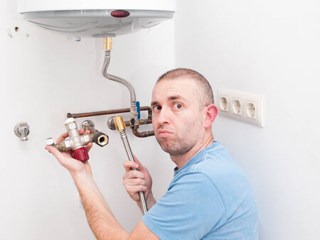 inexperienced: Inexperienced plumber trying to repair an electric water heater Stock Photo