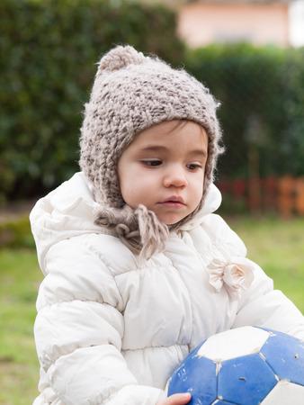 Pequeña muchacha con un sombrero de abrigo y de lana en invierno al aire libre