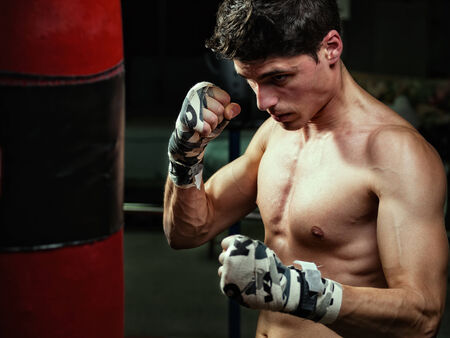 Young caucasian Boxer training with a punching bag in his home gym photo