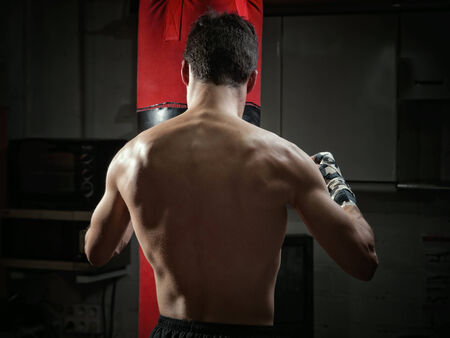 Young boxer back. The boxer is training with a punching bag. photo