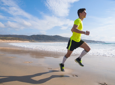 Young Man In Fitness Clothing Running Along Beach outdoors