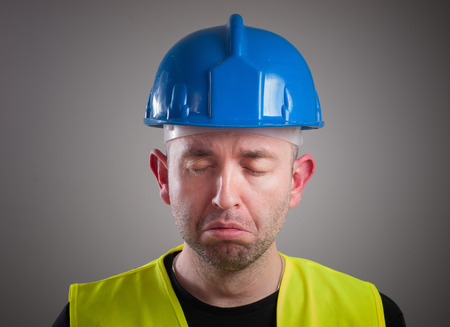 expressing negativity: Portrait of a worker expressing negativity and sad, isolated on dark background
