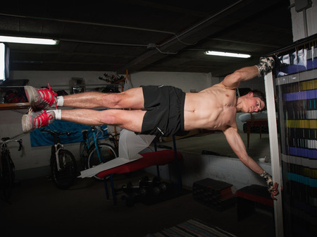 Man doing human flag exercise in a garage