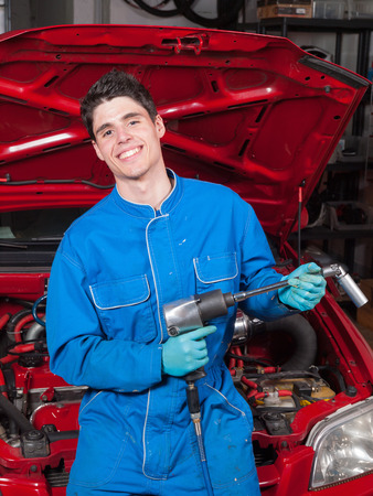 Mechanical smiling and holding a tool in a garage photo