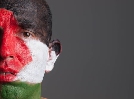 palestinian: Sad man and his face painted with palestine flag. The man is isolated on dark background. Stock Photo