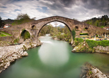 Old Roman stone bridge in Cangas de Onis (Asturias), Spain in a sunny day Imagens