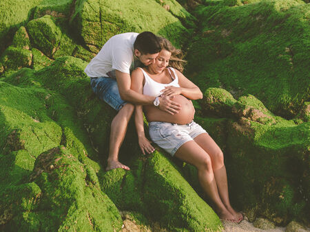 Happy Pregnant couple on beach outdoors.