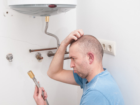 Inexperienced plumber trying to repair an electric water heater Stock Photo