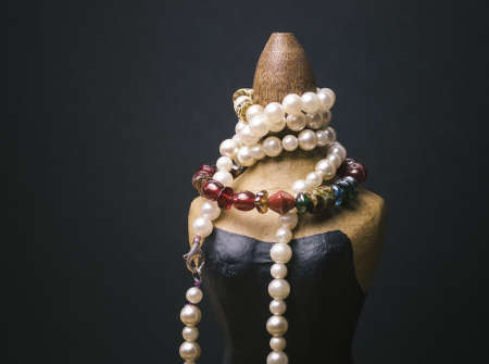 Miniature mannequin with necklaces isolated on dark background photo