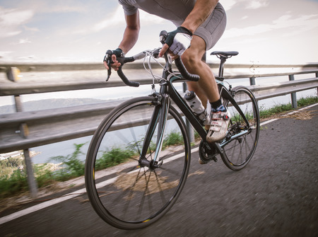 Detail of a road bike with a cyclist pedaling on a road. Stok Fotoğraf - 32827531
