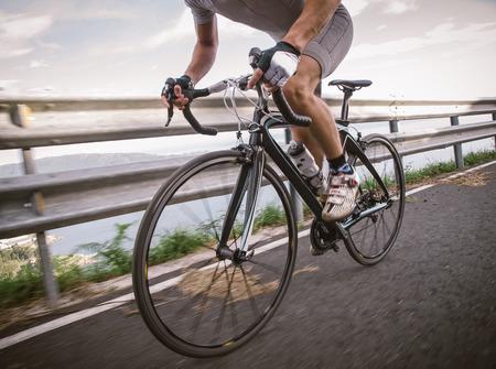 Detail van een racefiets met een fietser trappen op een weg.