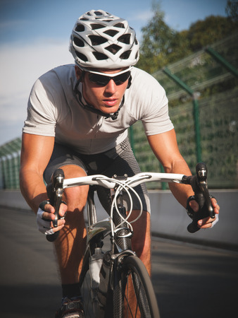Cyclist portrait in action on the road in a sunny day. photo