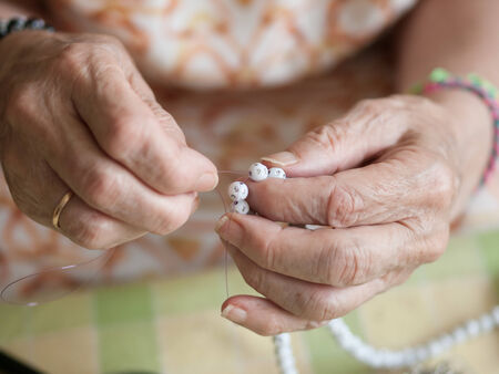 threading: Hands of elderly woman threading a necklace. Hands macro detail. Stock Photo