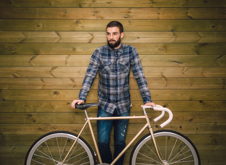 Hipster man with his fixie bike on a wooden background Stock Photo
