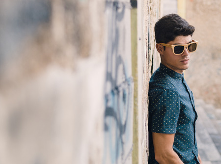 Fashionable man portrait over ruinous wall background outdoors photo