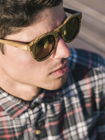 Model man portrait with wooden sunglasses outdoors in a sunny day photo
