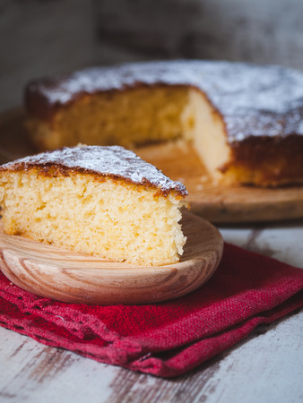 pound cake: Portion of a sponge cake on a wooden plate in a studio shot.