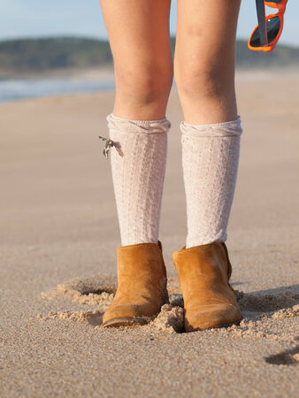 girl boots: Detail of little girl boots on the beach outdoors in a sunny day