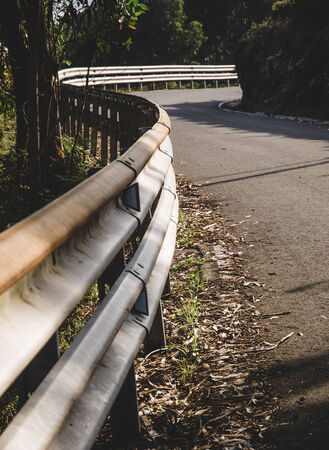 guardrail: Guardrail and curve in a road outdoors Stock Photo