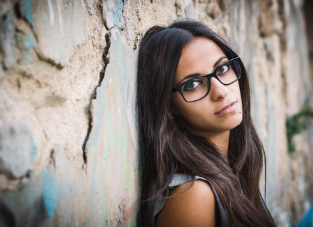 Beautiful brunette woman with sunglasses over a ruinous wall Imagens