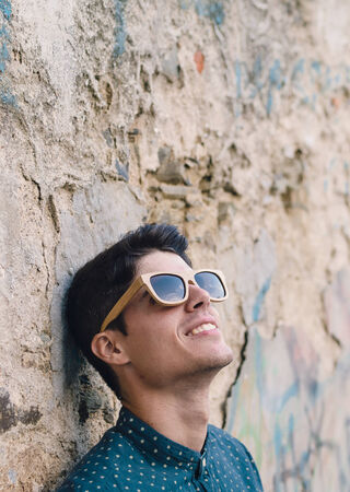 ruinous: Fashionable man portrait over ruinous wall background outdoors