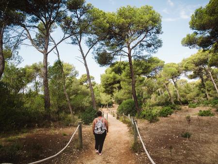 mediterranean forest: Woman walking in a path in a mediterranean forest in Menorca, Spain. Stock Photo