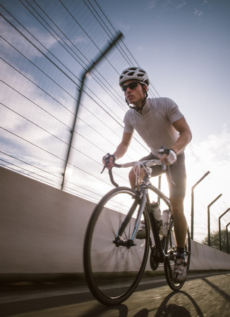 Cyclist in maximum effort in a road outdoors with backlight sunlight
