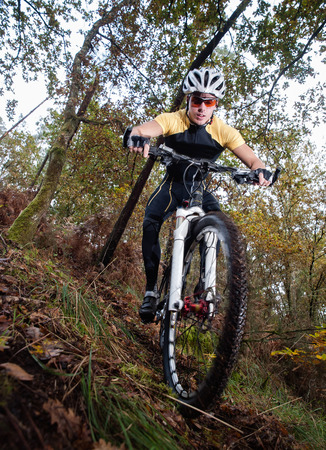 btt: Cyclist downhill in a forest outdoors. He is practicing mountain bike. Stock Photo